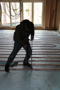 laying the water tubes for in floor heat in basement