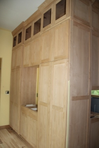 This cabinet is on the back side of the kitchen range.  It is a storage and serving piece for the outside dining room.