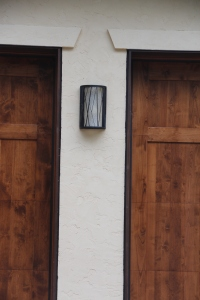 An outdoor light between the garage doors